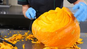 American holidays. All Hallows Day preparing. Closeup shot of hands in gloves carving from a pumpkin Jack-o. Cutting. Scary glowing halloween pumpkin . Special stock footage