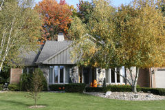American Home. Typical Amerian suburban home on a fall day; pumpkins on porch surrounded by colorful trees; Adrian Michigan American home lenawee county stock photo
