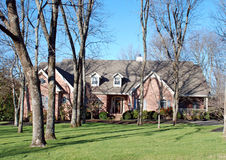 American Home on Wooded Lot 46. Modest one and a half story home behind thick tree cover Royalty Free Stock Photo