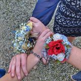 American Homecoming crosages and bracelets. Teen girls pose with hands interlocked displaying their flowers and jewelery from suiters before a homecoming dance stock image