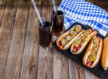 American hot dog with pickles,onions, ketchup, mustard and two soda Royalty Free Stock Photos