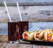 American hot dog with pickles,onions, ketchup, mustard and two soda Stock Photography