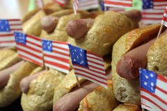American hot dogs with small American flags close plan, bun and sausage. American hot dogs with small American flags close plan, bun Royalty Free Stock Images