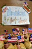 American hot dogs with small American flags close plan, bun and sausage and an inscription american hot dogs on paper. American hot dogs with small American Royalty Free Stock Photography