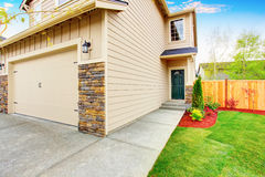 American house exterior with beige trim, garage with concrete driveway Royalty Free Stock Photography
