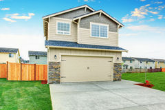 American house exterior with beige trim, garage with concrete driveway Royalty Free Stock Images