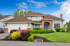 American house exterior with curb appeal. Classic house exterior with brick trimmed entrance porch, green lawn and trimmed hedges. Garage with driveway Stock Photography