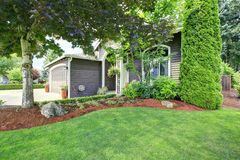 American house exterior with curb appeal. American house with landscape design. View of entrance porch and garage Stock Photography