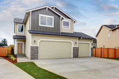 American house exterior with two garage spaces, concrete floor driveway. Royalty Free Stock Photography