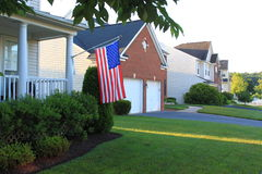 American Houses. In typical suburbs with single detached family houses, flag, and green lawn Stock Photography