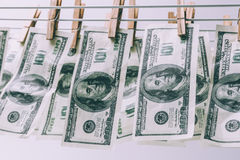 American hundred dollar bills hang on the dryer on clothespins. Money laundering stock photos