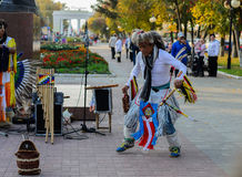 American Indian dancing. Street musician dressed as Native American dancing in the streets of entertaining guests and tourists Stock Photo