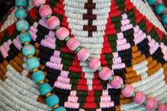 American Indian decor background - pink and turquoise beads draped on a colorful textile woven design closeup and shallow focus stock images