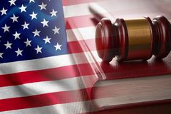 American justice and judiciary concept. With a wooden judges gavel on a law book in court overlaid with the flag of the United States stock image