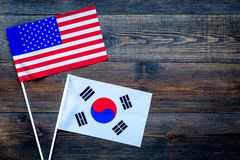 USA-Korea relations. Country cooperation. American and Korean flag on dark wooden background top view copy space royalty free stock photography