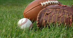 American leisure. Close up of a football, a baseball glove and a ball on the grass Royalty Free Stock Photos