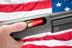 American loading shotgun. A man loads a shotgun shell into a pump action shotgun.  Shot against an American flag Royalty Free Stock Image