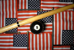 American Luck. An eight ball and a que stick with American flags for backdrops royalty free stock images