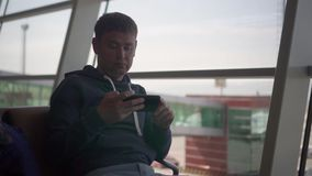 American male man sits in airport in panorman window an chair and looks app in phone. In order to check the gate.background a panorman window with buildings stock video footage
