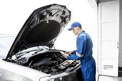 American mechanic repairing car with tablet. American male mechanic repairing a car by using a digital tablet while standing in the garage stock photos