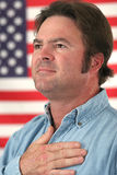 American Man Patriotic. A man in front of an American flag with his hand over his heart royalty free stock photo