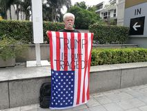 An American man show the American flag with the words `TRUMP IS OUR TRAGEDY.` On the Wireless road near the US embassy in Thailand. Bangkok-Thailand, 30/06/2017 Stock Photo