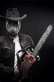 American maniac. With chainsaw in mask and cowboy hat posing over dark background royalty free stock photography