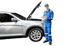 American mechanic with broken car and tablet. American male mechanic holding a digital tablet while repairing a broken car, isolated on white background royalty free stock photography