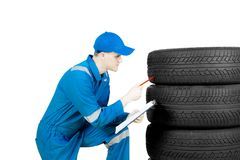 American mechanic with clipboard and tires on studio. Image of an American male mechanic squatting in the studio while checking tires and holding a clipboard Royalty Free Stock Photo