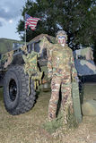 American Military. An American military figure in military camouflage is standing by an army vehicle with the American flag at dawn royalty free stock images