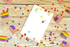 American mini and Pride Flags lie on a wooden background, top view, template for invitations and posters. Acceptance symbol. space. For text, space for copy stock image