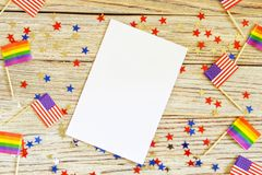 American mini and Pride Flags lie on a wooden background, top view, template for invitations and posters. Acceptance symbol. space. For text, space for copy stock photo