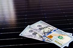 American money on solar panel surface. Renewable energy cost