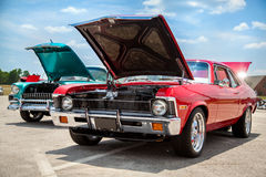 American muscle cars with the hoods open. Two old American 70s customized muscle cars with the hoods open on the show Stock Photo