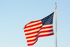 American National Flag Flitting in the Wind. On Blue Sky BAckground royalty free stock image