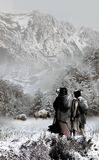 American Natives Approaching Buffalos. A couple of american natives with a baby approaching a couple of buffalos, in a cold and snowy landscape stock illustration