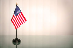 American office. American flag on a glass table, office like setting; copyspace royalty free stock image