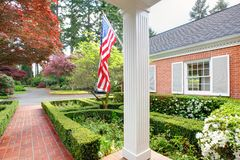 American old brick home with flag and classic garden. Royalty Free Stock Images