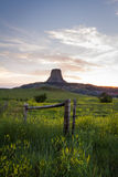 The American old west. Sunset including a farm and Devils Tower National monument , old west concept royalty free stock images
