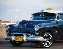 American Oldtimer in Cuba as Taxi. American Oldtimer parked in Cuba Havana on the promenade Royalty Free Stock Image