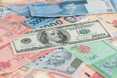 American one hundred dollar bills and Asian currencies background Royalty Free Stock Images