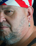 American Outlaw. Half facial shot of a rough biker type - an aging hippie with patriotic headwear and artist earring Royalty Free Stock Photos