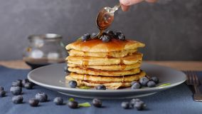 American pancake stack. Hd video shows a pancake stack topped with blueberries and how to add syrup with a spoon stock video