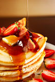 American pancakes. A picture of american style pancakes served with stawberries and bacon and topped with butter and maple syrup Stock Images