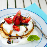 American pancakes. With cream, balsamic and fresh strawberries Royalty Free Stock Photography