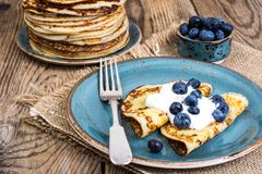 American pancakes with sauce and blueberries on wooden table top Stock Photo