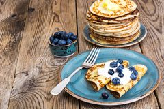 American pancakes with sauce and blueberries on wooden table top Royalty Free Stock Photos