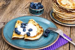 American pancakes with sauce and blueberries on wooden table top Royalty Free Stock Images