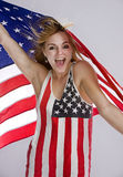American patriot. On a solid back ground a beautiful young blonde woman proudly shows her colors as she wears a flag tanktop and the wind whips the flag she is Royalty Free Stock Image