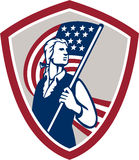 American Patriot Holding USA Flag Shield. Illustration of an American Patriot holding a USA stars and stripes flag set inside crest shield on isolated white Stock Image